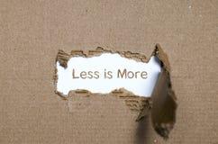 Le mot est moins plus apparaissant derrière le papier déchiré Image stock