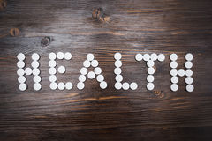 Le mot et le x22 ; health& x22 ; est présenté avec de grandes pilules blanches sur un fond en bois foncé Image libre de droits