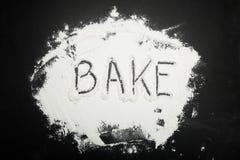Le mot font cuire au four est écrit sur la farine sur un fond noir photos stock