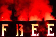 Le mot Free écrite avec le feu dans le métal barrels Photographie stock