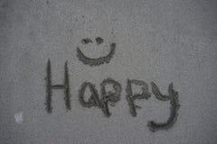 Le mot heureux avec un visage de smilie écrit dans le sable Images stock