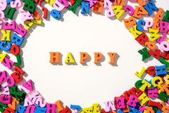 Le mot heureux est garni des lettres en bois colorées sur une table blanche avec dispersé en cercle avec des lettres Photo stock