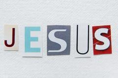 Le mot Jésus a coupé du journal sur la texture de papier fait main Photos libres de droits