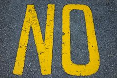 Le mot jaune AUCUN peint sur la rue Photos stock