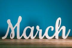 Le mot MARS - texte en bois au fond bleu-foncé contre les jeunes jaunes blancs de source de fleur de concept de fond Photos libres de droits