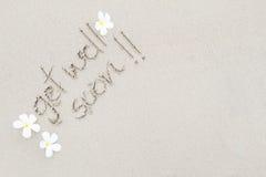 Le mot obtiennent le puits bientôt avec les fleurs blanches sur la surface b de plage Image stock