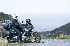 Le motard s'assied sur sa moto d'aventure, la montagne supérieure à l'arrière-plan, enduro, outre de la route, belle vue, route d images libres de droits