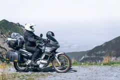 Le motard s'assied sur sa moto d'aventure, la montagne supérieure à l'arrière-plan, enduro, outre de la route, belle vue, route d image libre de droits