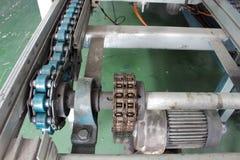 Le moteur et l'arbre d'entraînement à chaînes rayent le convoyeur industriel Photographie stock libre de droits