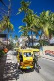 Le moto de tricycle roule au sol sur la route principale d'île de boracay à Philippines photos libres de droits