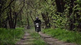 Le motocycliste chasse du coin sur des sports que la moto dans un casque chasse dans le chemin forestier clips vidéos