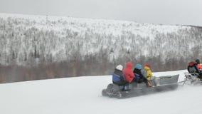 Le motoneige tire le bateau de banane gris de neige avec des voyageurs clips vidéos