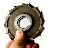 Le moulin bouleversé utilisé de dent de l'acier à outils s'est tenu dans la main gauche sur le fond blanc Photos stock