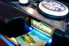 Le mouvement de la femme insère l'argent sur la machine à sous à l'intérieur de Casin photos stock