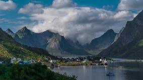 Le mouvement des nuages au-dessus de belles crêtes de montagne et un petit village de pêche en Norvège clips vidéos