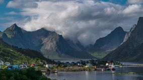 Le mouvement des nuages au-dessus de belles crêtes de montagne et un petit village de pêche en Norvège banque de vidéos
