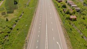 Le mouvement des voitures sur la route à proximité du village Longueur a?rienne banque de vidéos