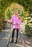 Le mouvement est bonheur Femme avec la bicyclette dans le jardin de floraison Activit? de week-end Loisirs et mode de vie actifs  image stock