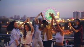 Le mouvement lent des mains de danse et de applaudissement des jeunes au dessus de toit de taille font la fête avec le disc-jocke clips vidéos