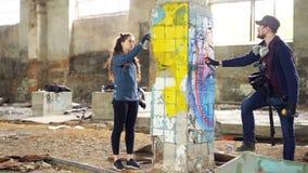 Le mouvement lent des peintres créatifs de graffiti partners décorer la maison abandonnée avec de belles images utilisant l'aéros clips vidéos