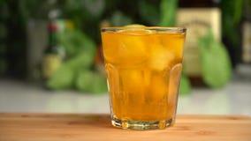 Le mouvement lent des tranches de chaux tombe dans le soda orange en verre avec de la glace banque de vidéos