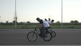 Le mouvement lent du groupe de cyclistes adolescents exécutant des tours de saut et le lapin sautent à cloche-pied utilisant des  banque de vidéos