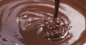 Le mouvement lent du noir de la meilleure qualité a fondu le chocolat étant versé de la cuillère dans la bonne partie du cadre Photo stock