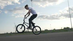 Le mouvement lent du plein vol de pratique pédalant et sautant de jeune cycliste se déplace avec le vélo dehors dans la rue - banque de vidéos