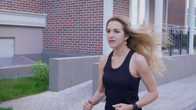 Le mouvement lent a tiré d'une jeune femme avec ses cheveux vers le bas, qui fonctionnent le long de la rue un jour d'été, elle c clips vidéos