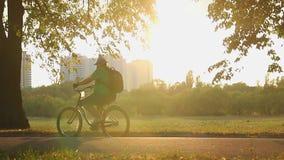 Le mouvement lent a tiré du vélo de poids excessif d'équitation d'homme en parc, problème d'obésité clips vidéos