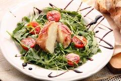 Le mozzarella a fait cuire au four en jambon de Parme avec de la salade de ressort d'arugula images libres de droits