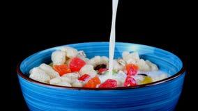 le muesli de céréale avec des flocons avec le fruit et les écrous est versé avec du lait clips vidéos