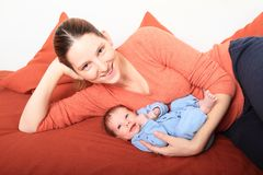 Le mumen med att le som är nyfött, behandla som ett barn flickan Royaltyfri Bild