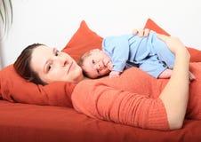 Le mumen med att le som är nyfött, behandla som ett barn flickan Arkivbilder