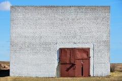 Le mur d'un immeuble de brique abandonné avec de grandes portes de garage photos libres de droits