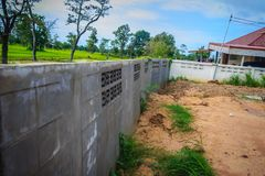 Le mur de barrière du logement nouvellement construit est incliné et du effondré Photographie stock libre de droits