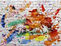 Le mur de briques blanc a souillé des taches de la peinture de différentes couleurs Image libre de droits