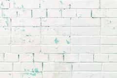 Le mur de briques est peint avec la peinture de épluchage blanche, de dessous laquelle une vieille couche de peinture de turquois photos stock