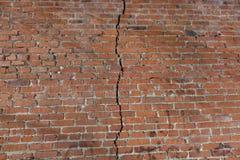Le mur de briques rouge est divisé par une fente verticale Concept de séparation photographie stock
