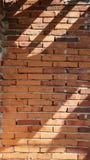 Le mur de briques rouge sous la lumière du soleil Photo stock