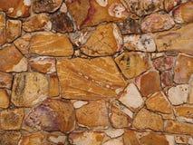 Le mur de briques rugueux de la terre et de la pierre a coloré le rocher Photo stock