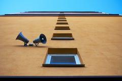 Le mur de la maison avec des fenêtres et des haut-parleurs Photo stock