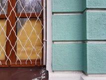 Le mur de la maison de ville, les blocs en pierre verts, une fenêtre avec un cadre en bois et un vintage metal le gril Photos stock