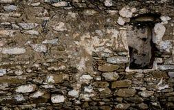 Le mur de la vieille pierre rugueuse avec un hublot Photographie stock libre de droits