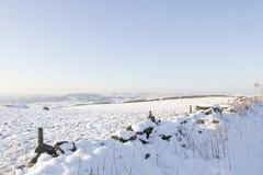 Le mur de pierres sèches de montagne et amarre couvert dans la neige Photo libre de droits