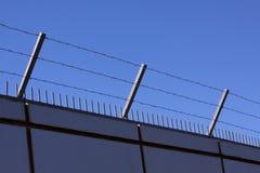 Le mur de sécurité avec le barbelé et les transitoires sur une barrière fournissent la sécurité - fond de ciel bleu photo stock