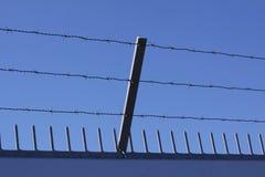 Le mur de sécurité avec le barbelé et les transitoires sur une barrière fournissent la sécurité - fond de ciel bleu image libre de droits