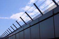 Le mur de sécurité avec le barbelé et les transitoires sur une barrière fournissent la sécurité - fond de ciel bleu photo libre de droits