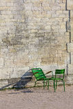 Le mur en pierre et deux chaises vertes dans Tuileries font du jardinage (la verticale) Photo stock