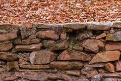 Le mur en pierre et sèchent des feuilles Images stock